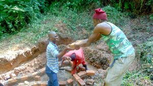 The Water Project:  Community Members Help Pass Bricks To The Artisan