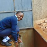 The Water Project: Kerongo Secondary School -  Happy Student With The Rain Tank