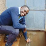 The Water Project: Kerongo Secondary School -  Happy Pupil At The Rain Tank