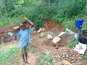 The Water Project:  A Child Carries Bricks To The Site
