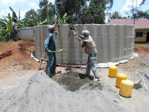 The Water Project:  Shoveling Cement Into Tank For Use