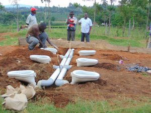 The Water Project:  Affixing Latrine Recepticles Into Pit Holes