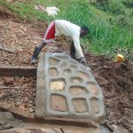 The Water Project: Jivovoli Community, Magumba Spring -  Rub Wall Construction