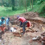 The Water Project: Bumira Community, Imbwaga Spring -  Passing Bricks To The Artisan