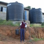 The Water Project: Kimuuni Secondary School -  Student And Small Rainwater Tanks