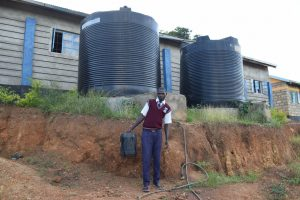 The Water Project:  Student And Small Rainwater Tanks