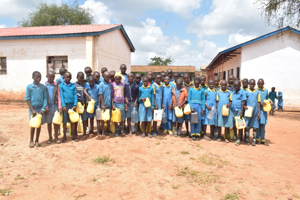The Water Project : kenya20354-students-holding-the-water-containers-they-bring-from-home
