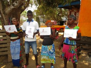 The Water Project:  Participants Hold Up Training Materials