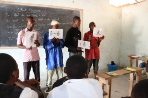 The Water Project:  Participants Hold Up Disease Transmission Posters