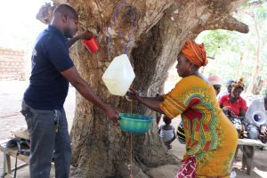 The Water Project:  Old Woman Displaying How To Do Handwashing With Tippy Tap