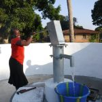 The Water Project: Lungi, Lungi Town, Holy Cross Primary School -  Teacher Pumping Water