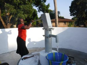 The Water Project:  Teacher Pumping Water
