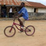The Water Project: Sulaiman Memorial Academy Jr. Secondary School -  Student Riding Bike To Home