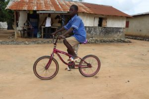 The Water Project:  Student Riding Bike To Home