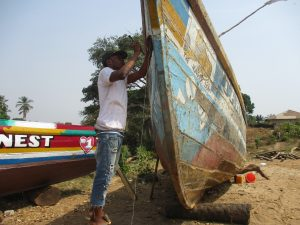 The Water Project:  Young Man Repearing Boat