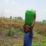 The Water Project: Lokomasama, Gbonkogbonko Village -  Small Boy Carrying Water