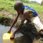 The Water Project: Lokomasama, Kennenday Village -  Small Boy Collecting Water