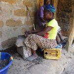 The Water Project: Lokomasama, Kennenday Village -  Woman Breaking Palm Kernel