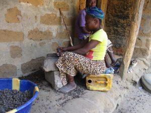 The Water Project:  Woman Breaking Palm Kernel