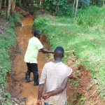 The Water Project: Kitulu Community, Kiduve Spring -  Opening Drainage Channel