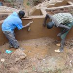 The Water Project: Kitulu Community, Kiduve Spring -  Plastering Inside Headwall