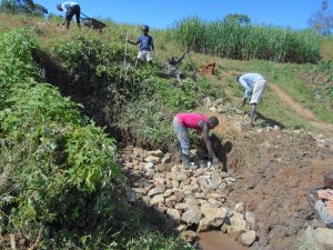 The Water Project:  Community Helps Backfill With Stones
