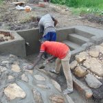The Water Project: Emurumba Community, Makokha Spring -  Cementing Stone Pitching