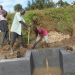 The Water Project: Kalenda A Community, Webo Simali Spring -  Passing Clay To The Artisan