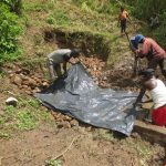The Water Project: Rosterman Community, Lishenga Spring -  Adding Plastic Tarp To Backfilling
