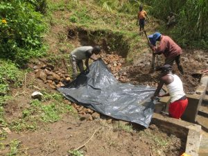 The Water Project:  Adding Plastic Tarp To Backfilling