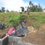 The Water Project: Kalenda A Community, Webo Simali Spring -  Laying Tarp Over Stones