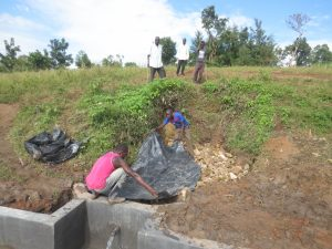The Water Project:  Laying Tarp Over Stones