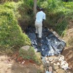 The Water Project: Kalenda B Community, Lumbasi Spring -  Adding The Tarp Over Backfill