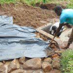 The Water Project: Maondo Community, Ambundo Spring -  Adding Plastic Tarp Over Stones