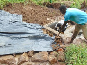 The Water Project:  Adding Plastic Tarp Over Stones