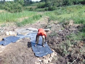The Water Project:  Adding Tarp Over Backfilled Stones
