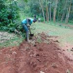 The Water Project: Kitulu Community, Kiduve Spring -  Digging Cut Off Drainage Above Spring