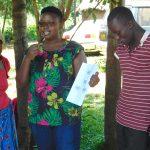 The Water Project: Namarambi Community, Iddi Spring -  Jacky Uses A Training Poster