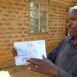 The Water Project: Mwichina Community, Matanyi Spring -  Using Training Poster To Mkae A Point