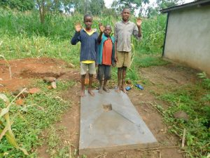 The Water Project:  Kids Stand With Their Familiys New Sanitation Slab