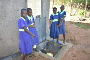 The Water Project:  Girls Pose With Rain Tank