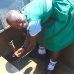 The Water Project: Bumbo Primary School -  Student Enjoying Rain Tank Water