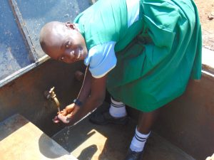 The Water Project:  Student Enjoying Rain Tank Water