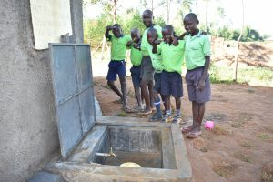 The Water Project:  Boys Pose With Rain Tank