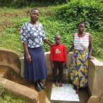 The Water Project: Mwichina Community, Matanyi Spring -  Field Officer Betty With Moses And Agnetta