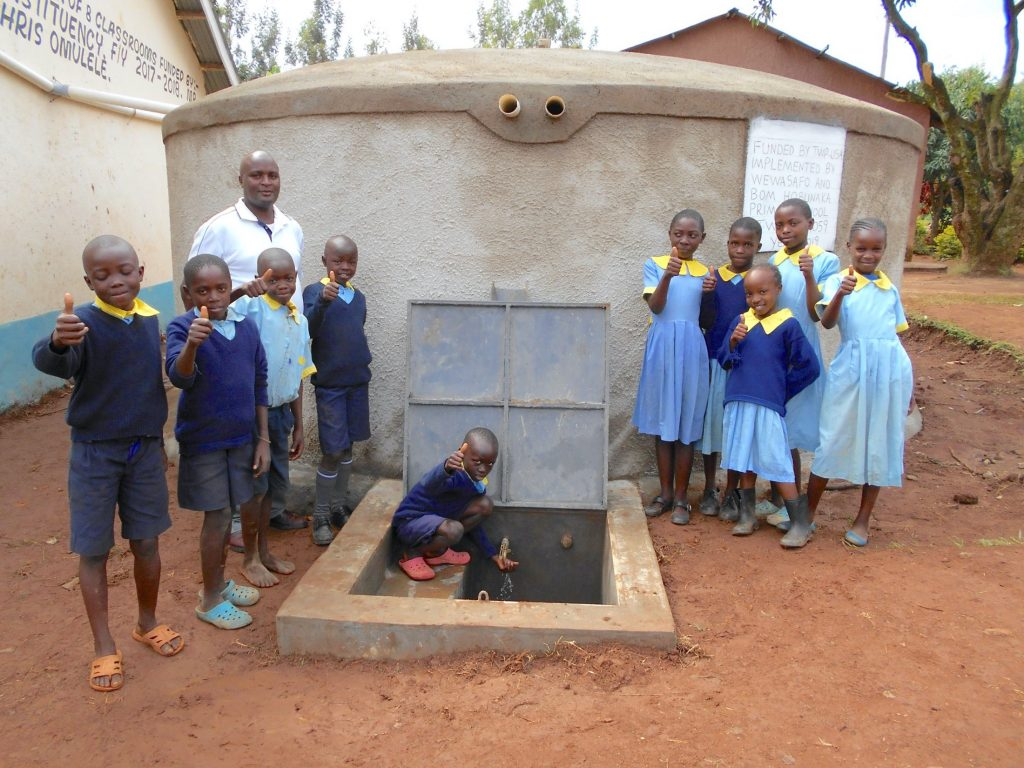 The Water Project : 48-kenya19059-pupils-and-staff-pose-with-rain-tank