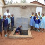 The Water Project: Hobunaka Primary School -  Pupils And Staff Pose With Rain Tank