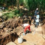 The Water Project: Namarambi Community, Iddi Spring -  Passing Bricks To Artisan