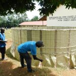 The Water Project: Hobunaka Primary School -  Tying Sugar Sacks To Wire