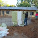 The Water Project: Saride Primary School -  Attaching Sugar Sacks To Wire